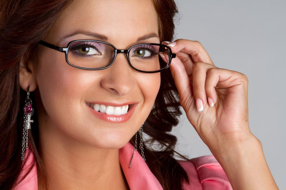 Woman smiling with her new glasses because she had her vision problems treated by her winnipeg eye doctor